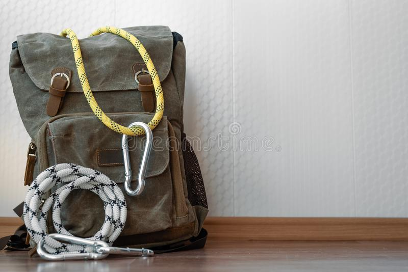 Travel. A backpack with safety rope and carabiners on a white wall background . Travel or adventure background, alpinism, climber, rock, tourist, tourism stock photo