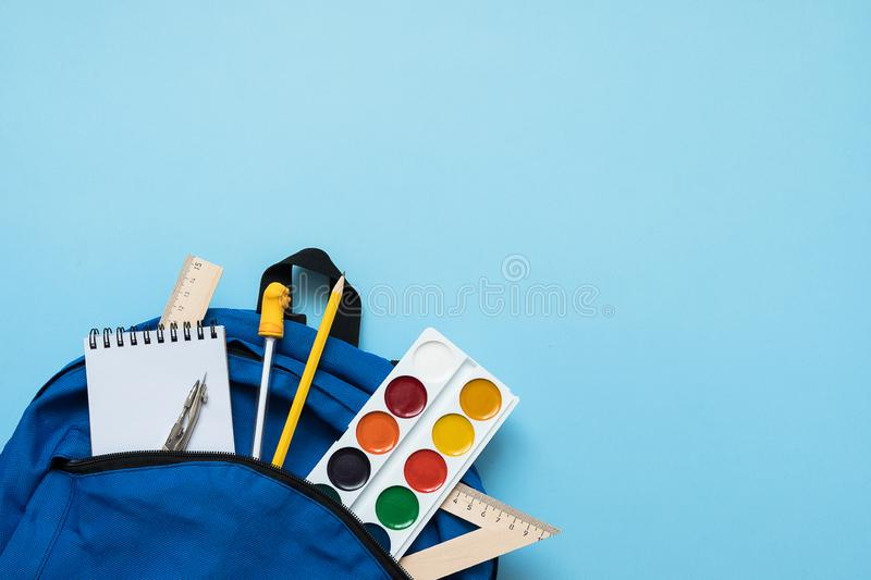 Backpack with school supplies, isolated on blue royalty free stock image