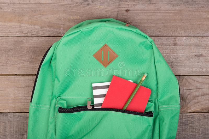 Backpack and school supplies notepad, pencil on brown wooden table royalty free stock photo