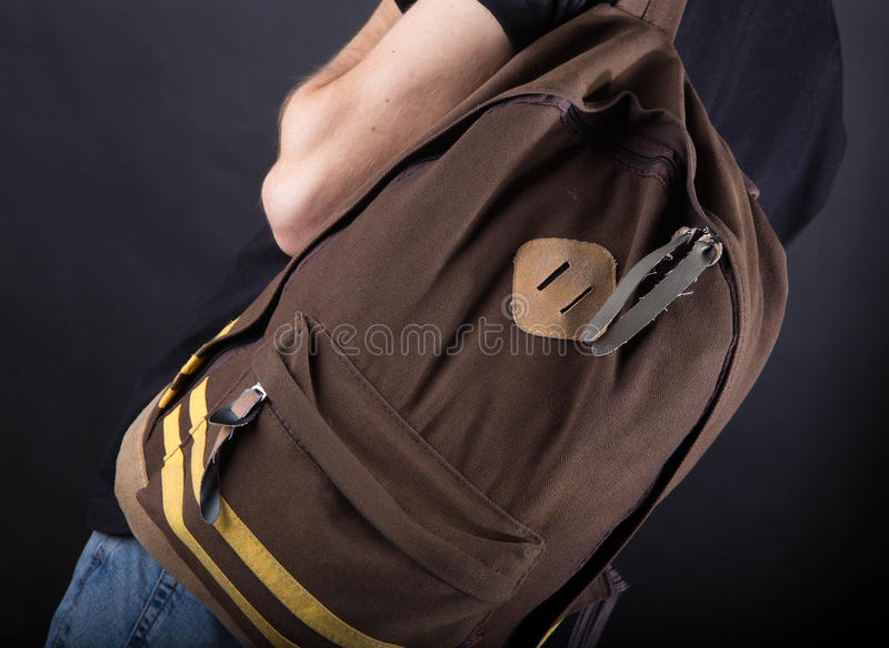 Backpack on the shoulder of a young man on a black royalty free stock photos