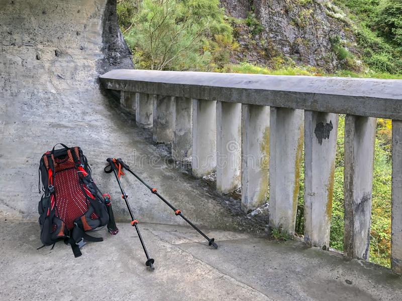 Backpack and trekking sticks, hiking poles on background of nature, rock mountains and reinforced concrete railing. Backpack and trekking sticks, hiking poles on stock images
