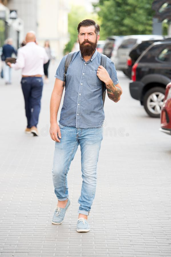 Backpack for urban travelling. Hipster wearing backpack urban street background. Bearded man travel with backpack. Guy stock image