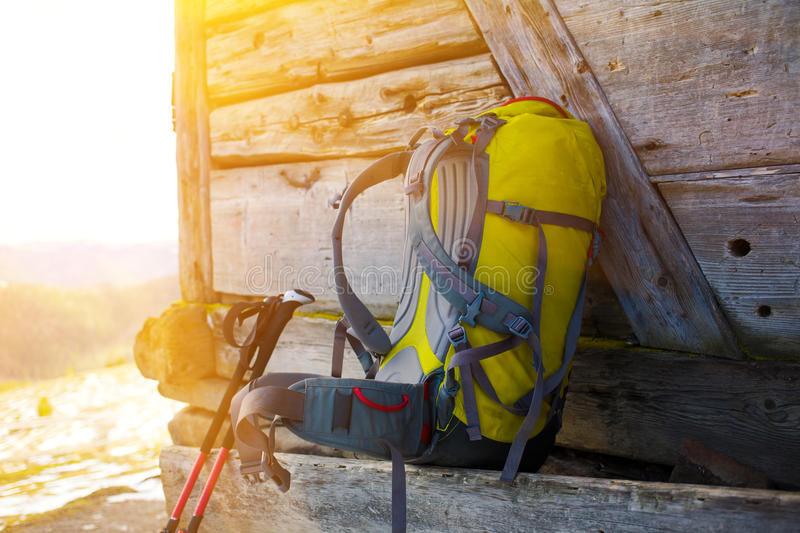 The backpack and walking sticks. Walking sticks and backpack standing on the bench near the wooden house royalty free stock photography