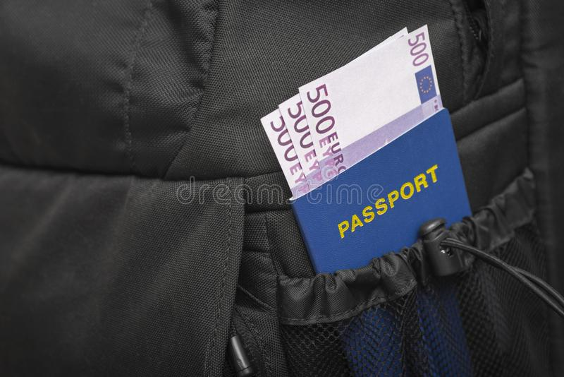 A backpack from whose pocket a passport and money are sticking out in euros stock images