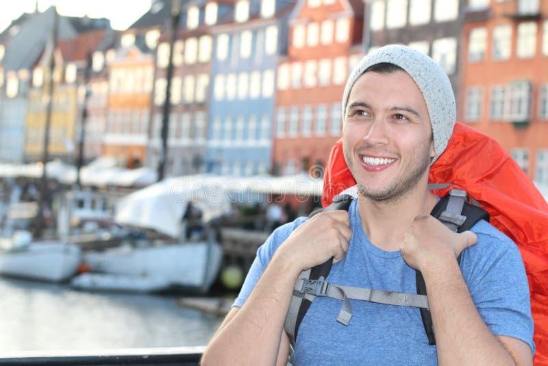 Backpacker étnico que sonríe en el Nyhavn épico, Copenhague, Dinamarca foto de archivo libre de regalías