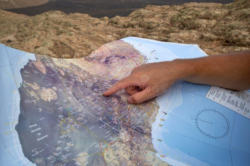 Backpacker που ψάχνει μια διαδρομή στο χάρτη τουριστών στοκ εικόνες