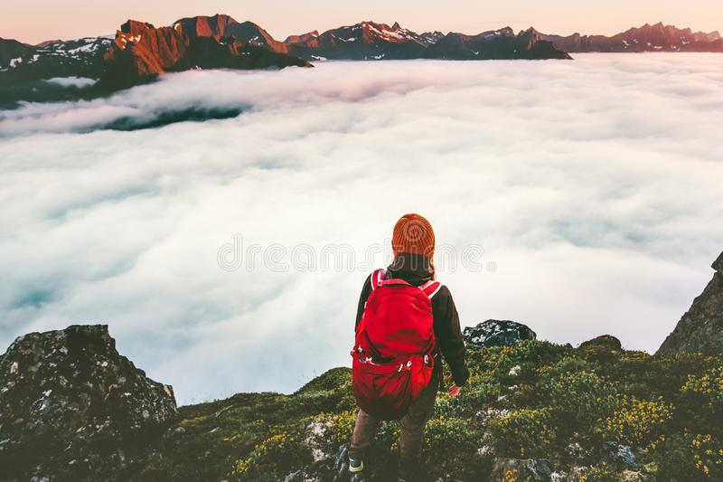 Backpacker авантюриста на скале над облаками в горах захода солнца стоковые фото