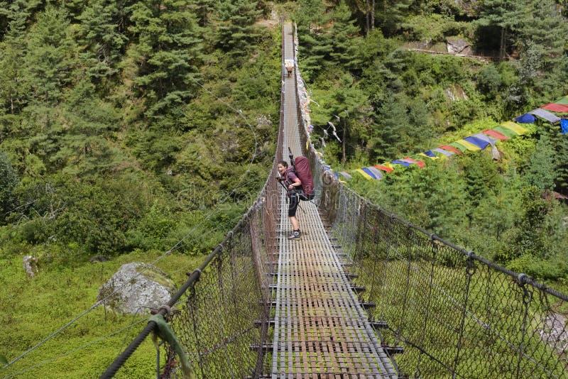 Backpacker женщины на trekking пути пересекая приостанавливанный мост стоковые фото