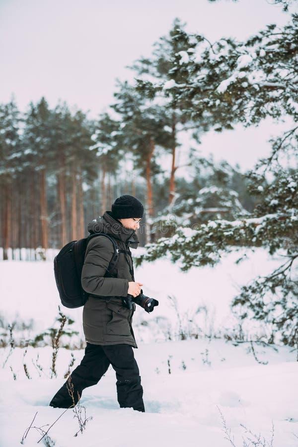 Backpacker молодого человека с камерой фото принимая фото в хобби леса Snowy зимы активном Hiker идя в Snowy стоковые изображения rf