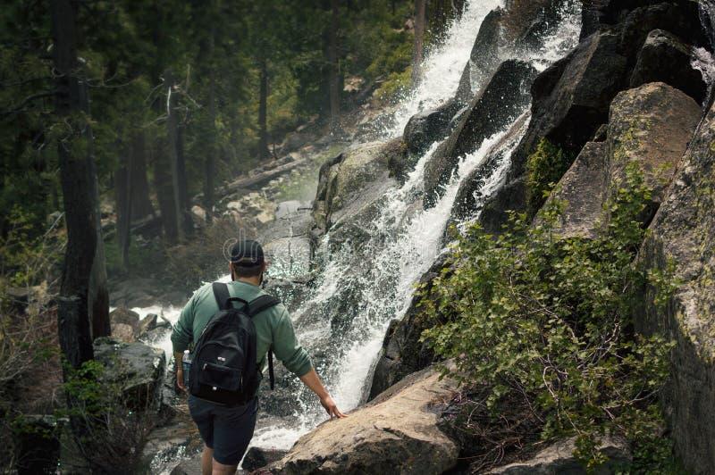 Backpacker al bordo della cascata Sceneggiatura che ispira una vista naturale catartica fotografia stock