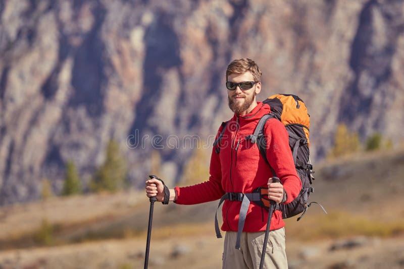 Backpacker alto con los polos a disposición fotos de archivo