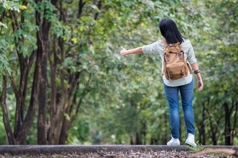 Backpacker asiático de la mujer que se coloca en el camino del campo con el árbol adentro foto de archivo libre de regalías