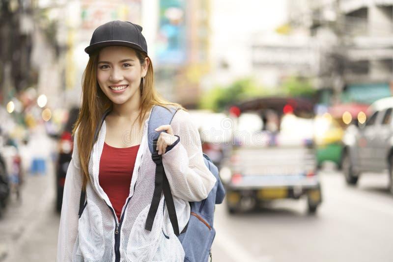 Backpacker asiático joven del bolso del viajero de la mujer en la calle en el mercado al aire libre del camino de Yaowarat en Ban imagen de archivo