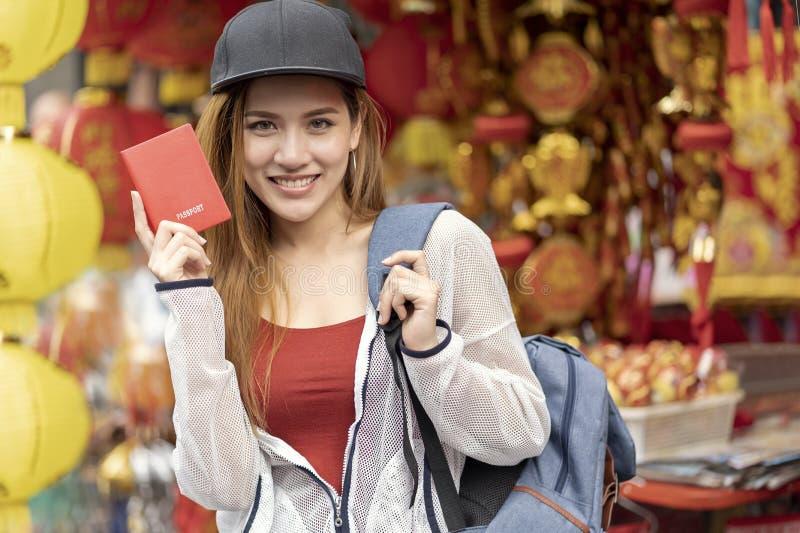 Backpacker asiático joven del bolso del viajero de la mujer que sostiene el pasaporte rojo para las vacaciones del viaje del viaj fotografía de archivo libre de regalías