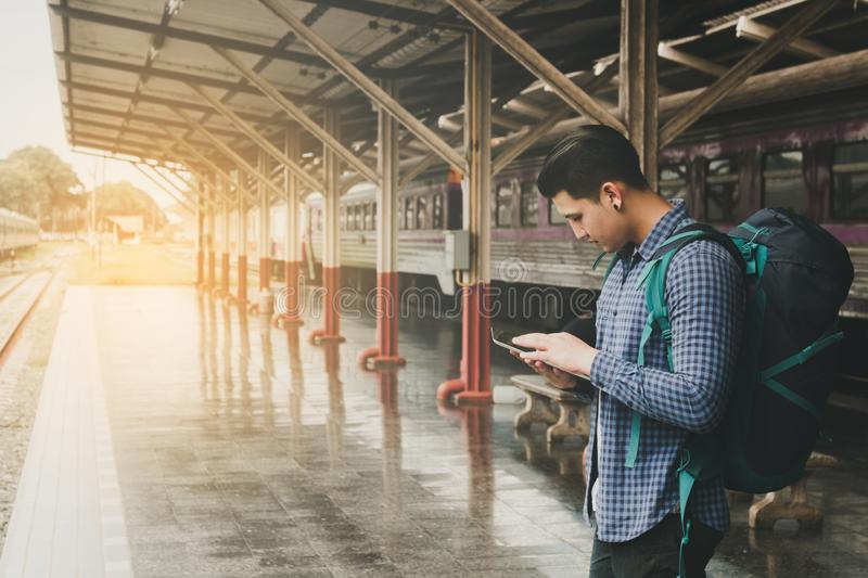 Backpacker asian man using tablet searching map location with tr royalty free stock image