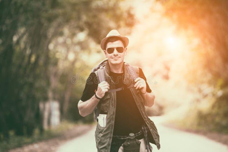 Backpacker caucásico del hombre joven que viaja en campo local foto de archivo