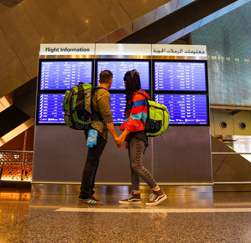 Backpacker couple at the airport in Doha. Backpacker couple looking flight information at the airport in Doha stock photos