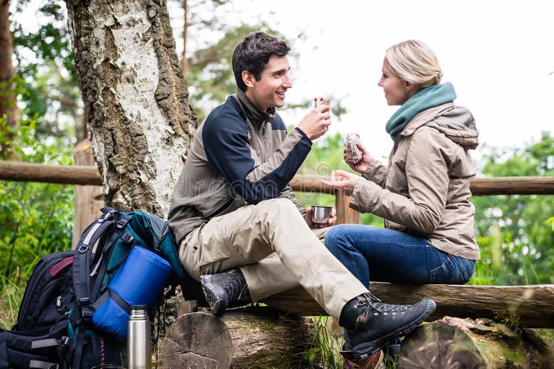 Backpacker couple taking rest aside hiking trail. Having coffee and sandwiches stock photos