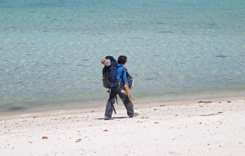 Backpacker de la muchacha que recorre en una playa fotografía de archivo libre de regalías