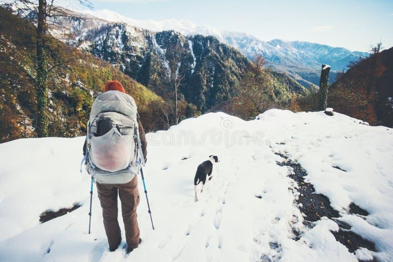 Backpacker de la mujer con el perro que camina las montañas del invierno imagenes de archivo