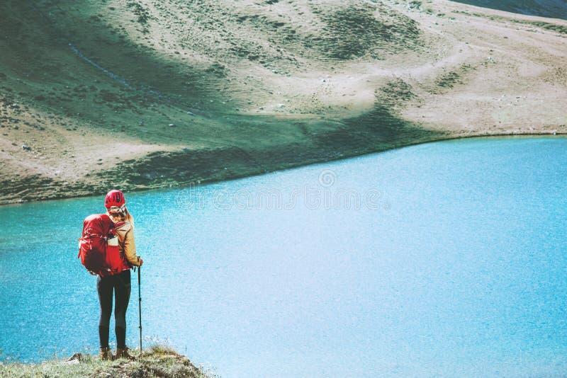 Backpacker de la mujer en el acantilado sobre el lago imagen de archivo