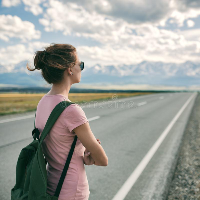 Backpacker de la mujer joven que camina en el camino fotografía de archivo libre de regalías