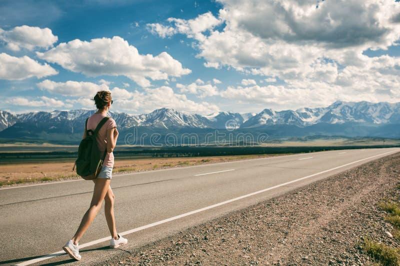 Backpacker de la mujer joven que camina en el camino imagen de archivo