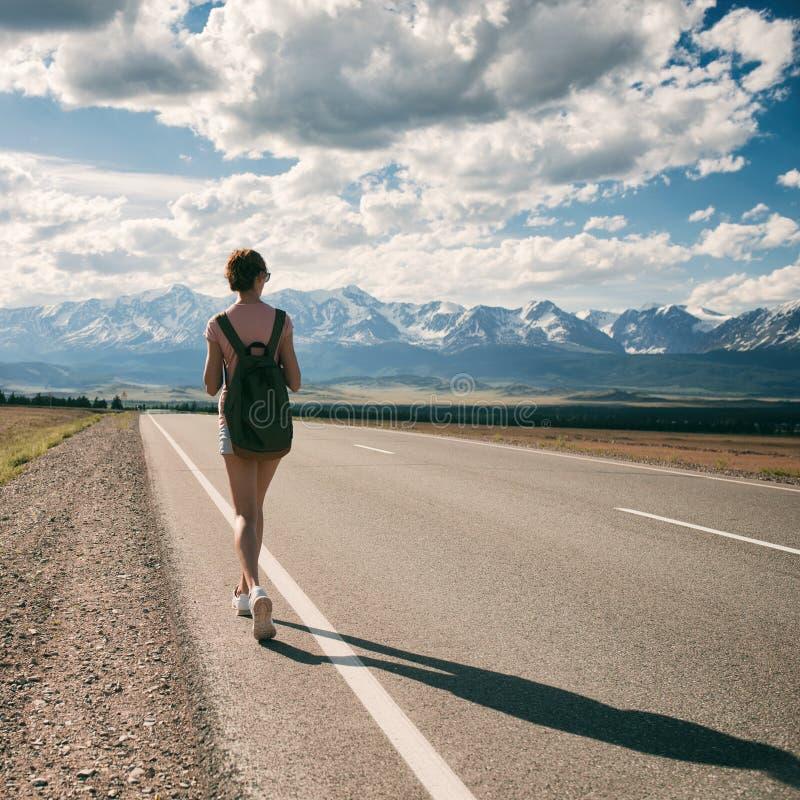 Backpacker de la mujer joven que camina en el camino fotografía de archivo