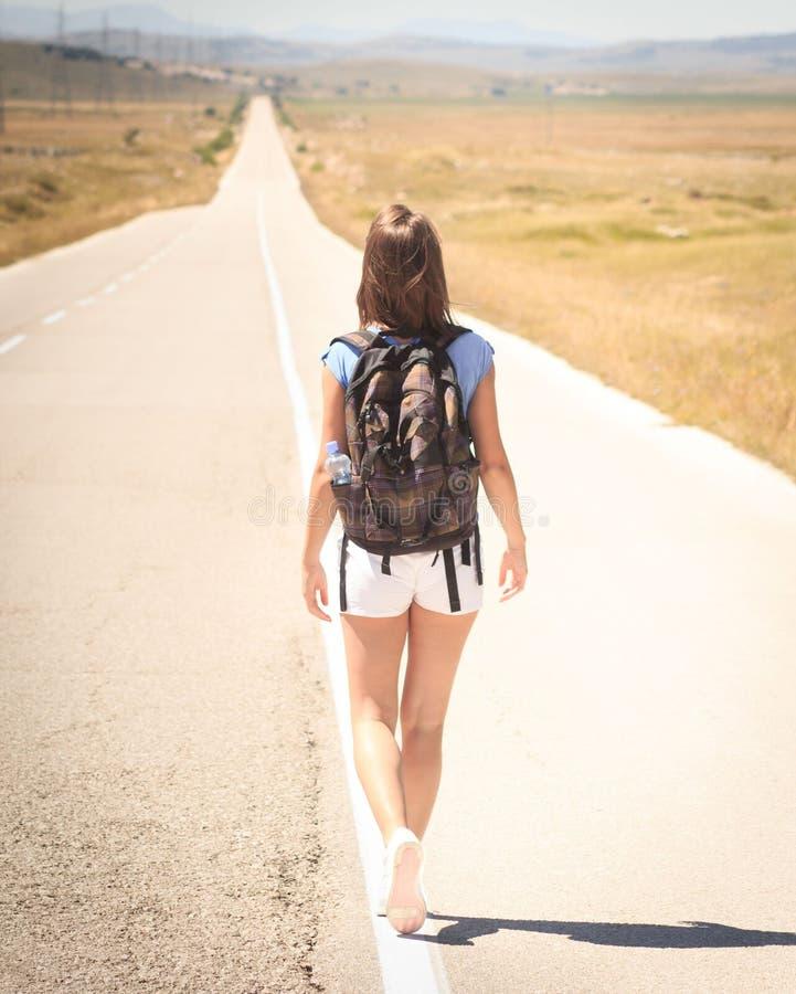 Backpacker de la mujer que camina en el camino fotografía de archivo