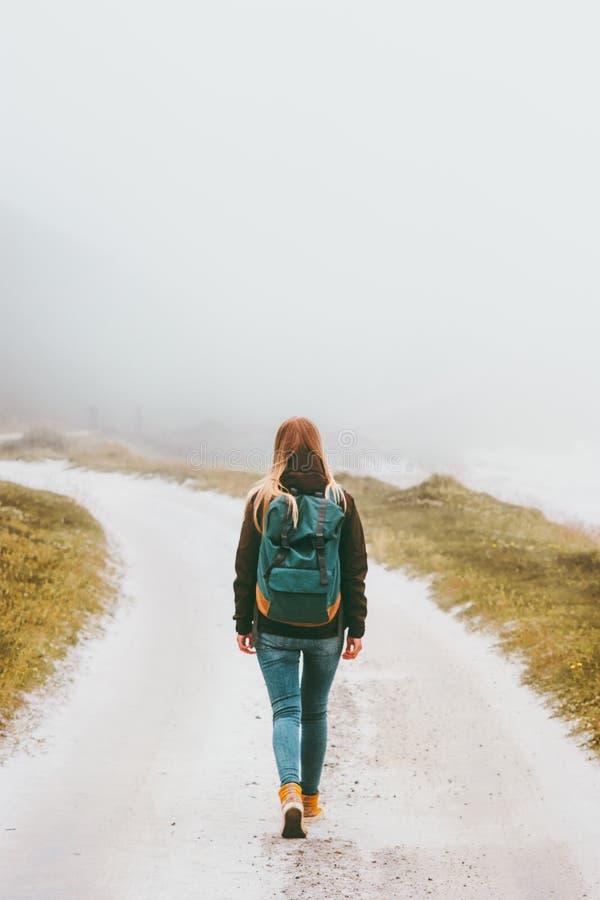 Backpacker de la mujer que camina solamente en el camino de niebla foto de archivo