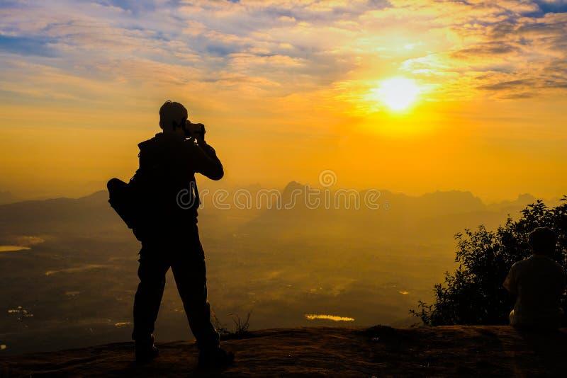 Backpacker del hombre con su silueta de la cámara del dslr en puesta del sol imagen de archivo libre de regalías