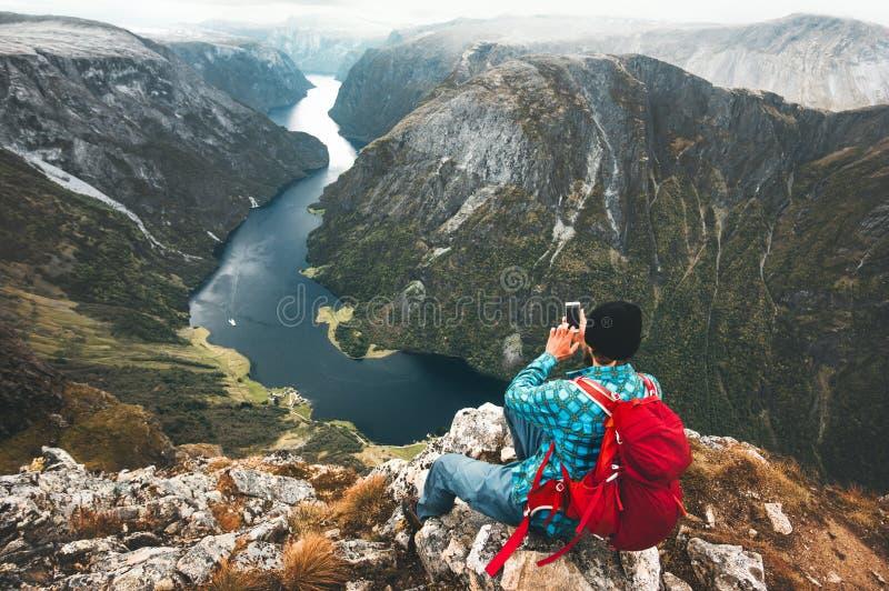 Backpacker del hombre que usa el smartphone que se relaja en el top de la montaña imagen de archivo