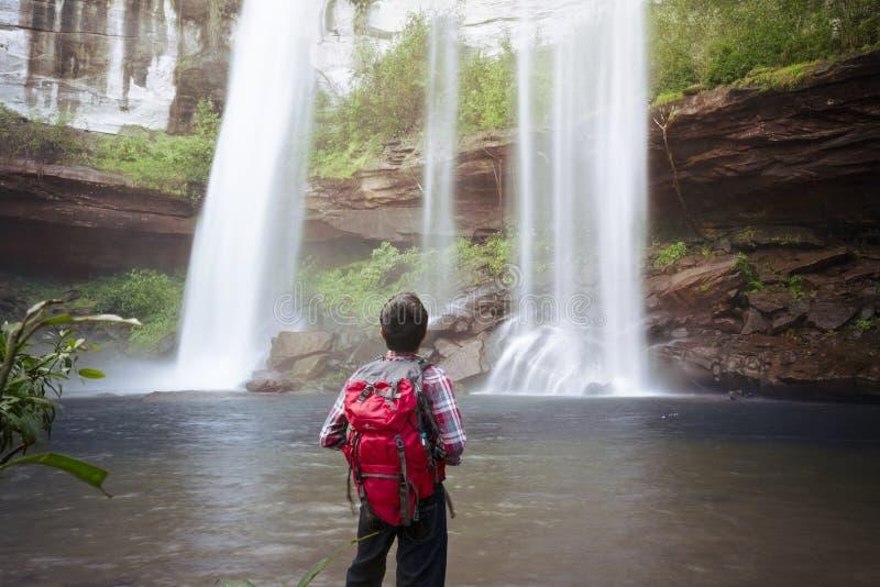 Backpacker die zich voor waterval bevinden royalty-vrije stock afbeelding