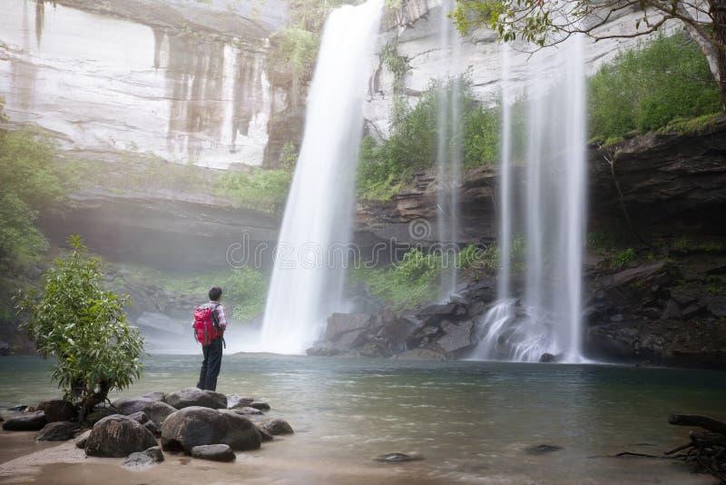 Backpacker die zich voor waterval bevinden royalty-vrije stock foto
