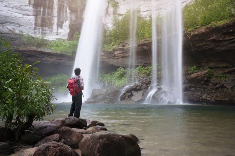 Backpacker die zich voor waterval bevinden royalty-vrije stock foto's