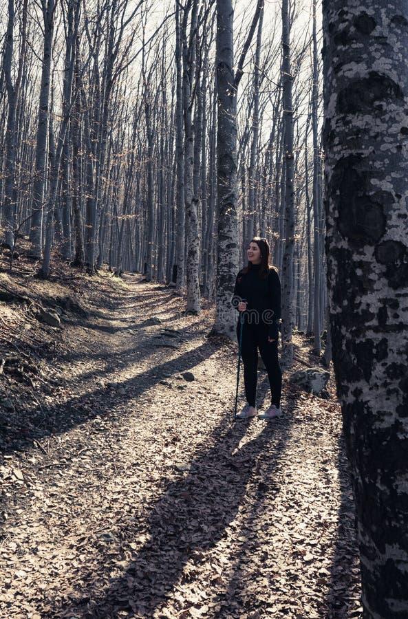 Backpacker dziewczyna uśmiecha się wycieczkować w lesie z kijem obrazy stock