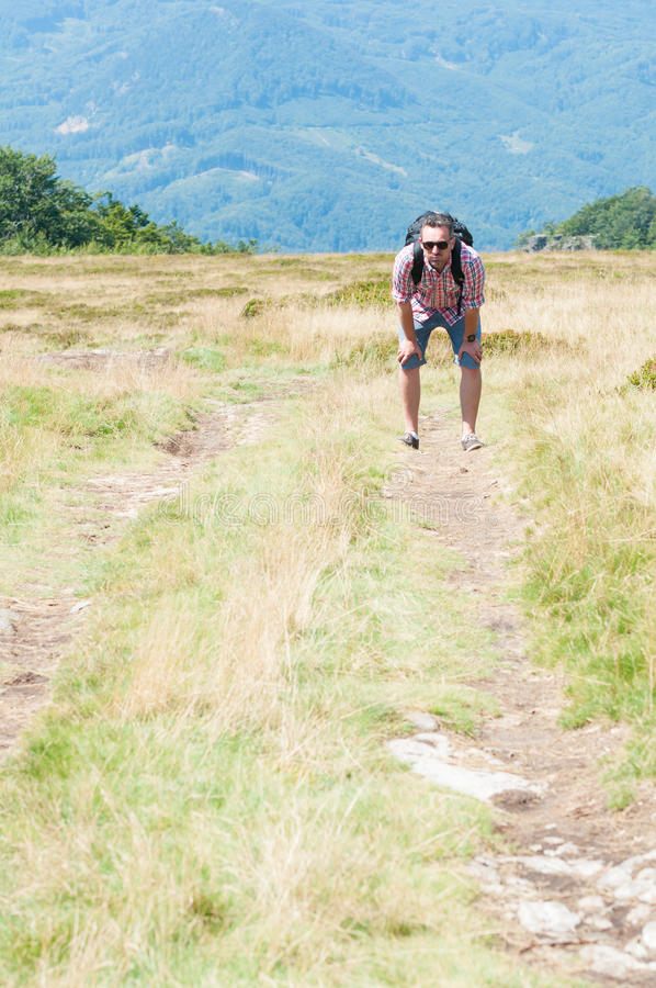 Backpacker en el sendero de la montaña que siente cansado fotografía de archivo libre de regalías