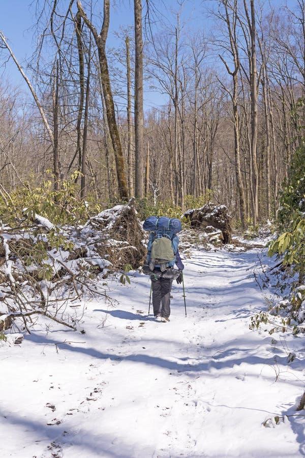 Backpacker en un rastro Nevado después de una nieve de la primavera foto de archivo libre de regalías