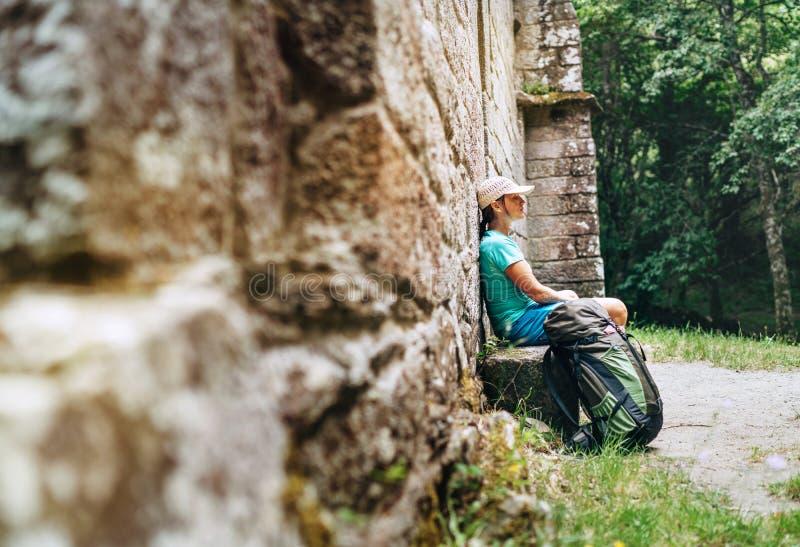 Backpacker femenino cansado que descansa sobre el banco cerca del castillo antiguo viejo de la pared de ladrillo en la manera fam fotografía de archivo libre de regalías