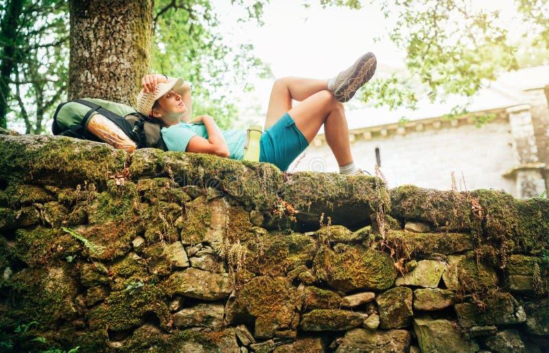 Backpacker femenino joven pacífico durmiente liying en el fance de piedra viejo del castillo y que disfruta de un rato de resto e imagen de archivo libre de regalías