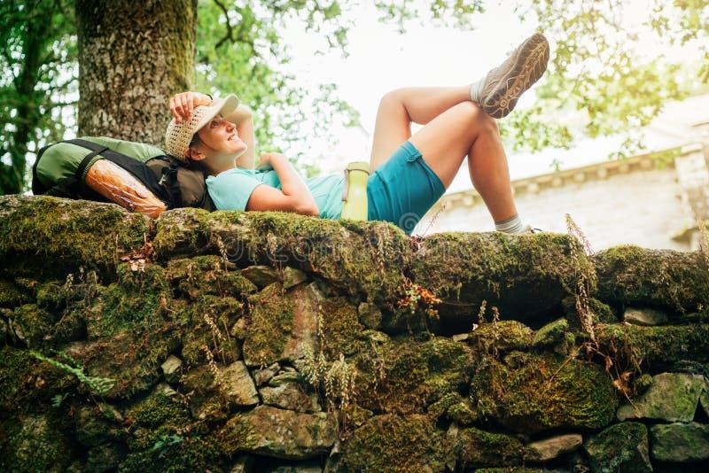 Backpacker femenino joven sonriente alegre liying en el fance de piedra viejo del castillo y que disfruta de un rato de resto en  imagen de archivo