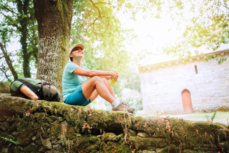 Backpacker femenino joven sonriente alegre que se sienta en el fance de piedra viejo del castillo y que disfruta de un rato de re imágenes de archivo libres de regalías
