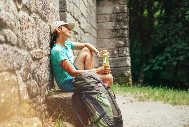 Backpacker femenino muy cansado que descansa sobre el banco cerca del castillo antiguo viejo de la pared de ladrillo en la manera foto de archivo