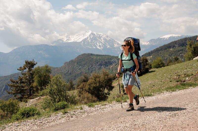 Backpacker femenino que va abajo del camino en colinas fotos de archivo