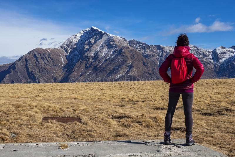 Backpacker girl in the alps. A backpacker in the italian alps in Valsassina area in fron of mount legnone stock images