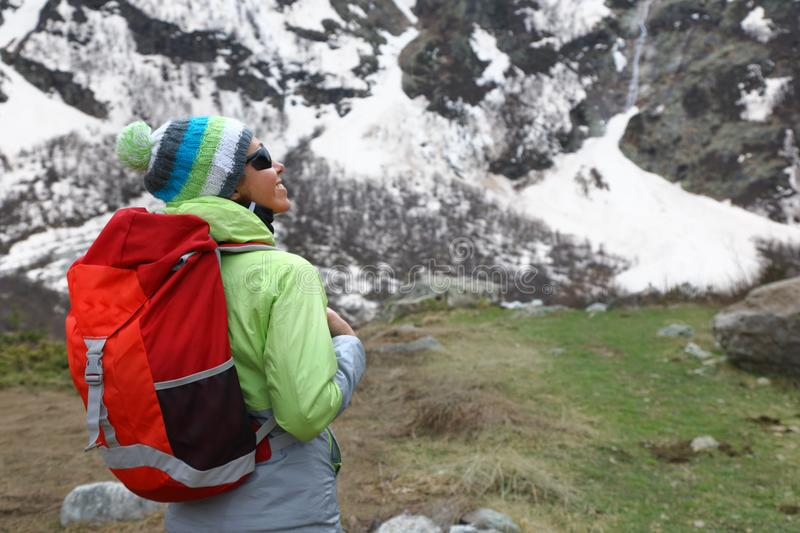 Backpacker girl stands on top of a mountain royalty free stock photography