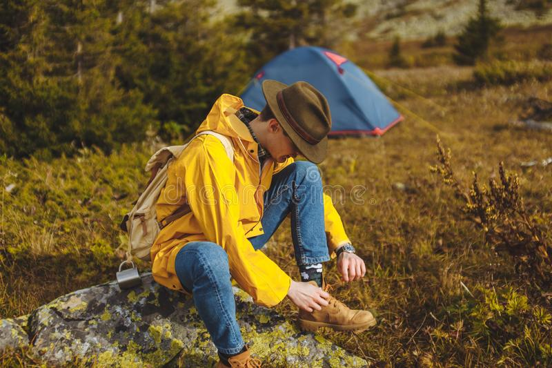 Backpacker in green hat, yellow coat laces shoes. Preparing for walking. cose up side view photo. copy space, tent in the background of the photo royalty free stock images