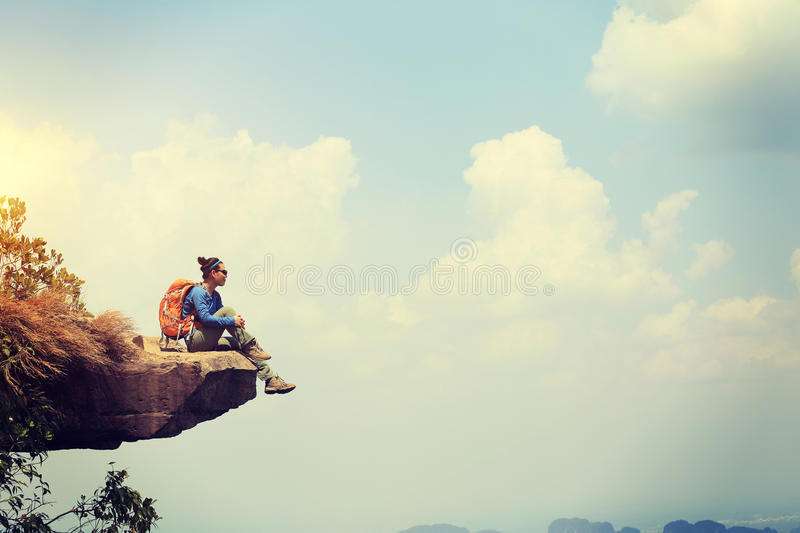 Backpacker hiking on mountain peak cliff. Young woman backpacker hiking on mountain peak cliff stock photography