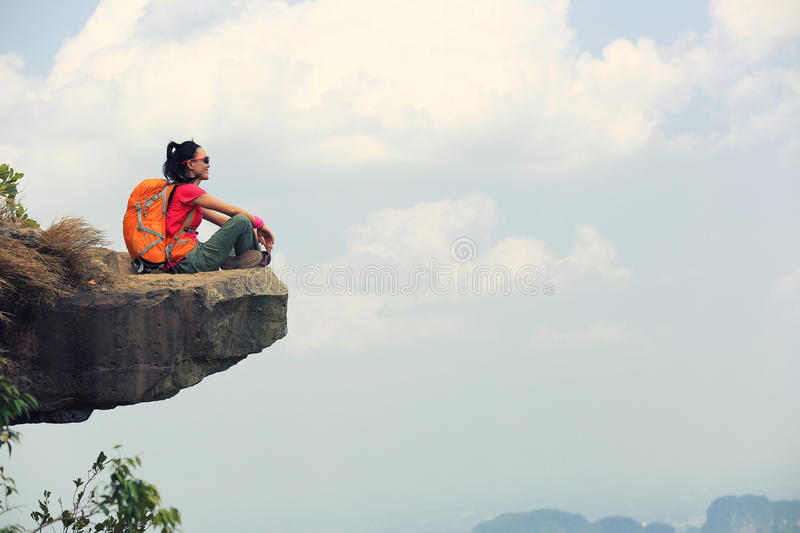 Successful young woman backpacker sit on the cliff edge on mountain top. Enjoy the view stock images