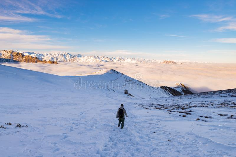 Backpacker hiking on snow on the Alps. Rear view, winter lifestyle, cold feeling, majestic mountain landscape. stock photo